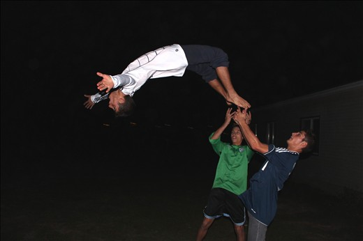 Aiming High: young men show off their acrobatic skills for a young female visitor to their countryside home.
