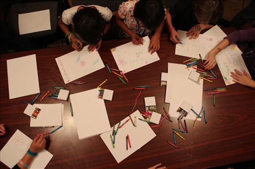Rainbows: crayons and paper are strewn over the table at a girls' home after dinner, a time to explore creativity and complete homework.