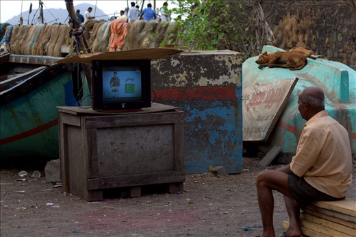 The fisherman watching a classic Amitabh Bachaan movie, right on the dockyard.
