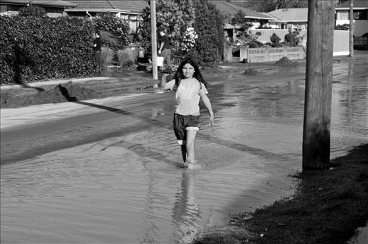 A young child enjoying the silver lining of flooded streets.