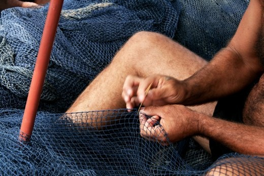 Repair of the seemingly endless netting requires nimble fingers and tireless precision; this fisherman has perfected these skills through decades of work in the village.