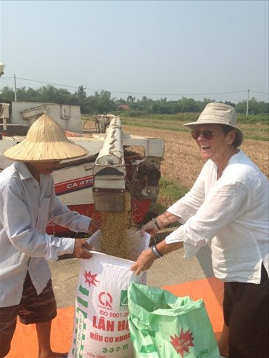 Monika helping the man fill the bags with rice from the harvester.