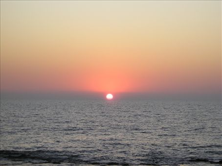 The sun sets on a Goan beach.