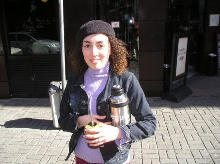 A Uruguayan girl with her Mate kit. Note the thermos and the cup with green mush in it.