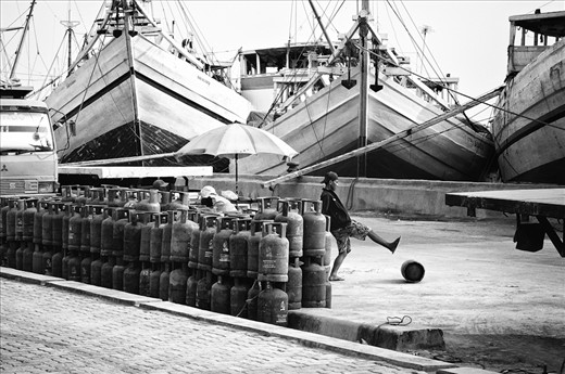 At the Sunda Kelapa harbor (Jakarta), the longshoremen transfer the gas cylinders by kicking them. Working days that pass one after the other, all the same, so inured to risks that they don't even care about anymore.