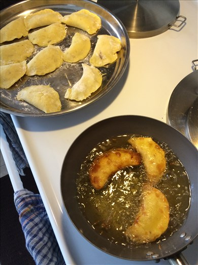 Sweet potato dough rounds shaped in a semicircle and fried