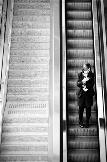 Watch Your Step. The woman is getting down using the escalators but she is focusing with her phone. So becareful.. watch your step girl..