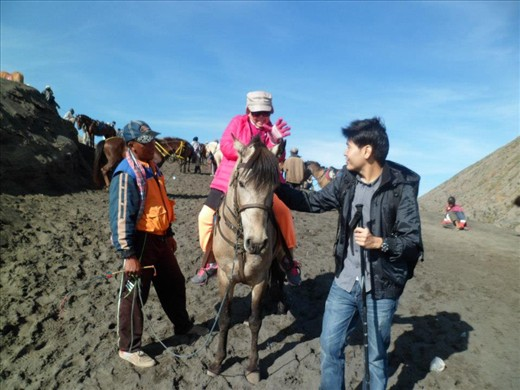 Win is helping his sweet pink-mother to ride a horse down from the crater
