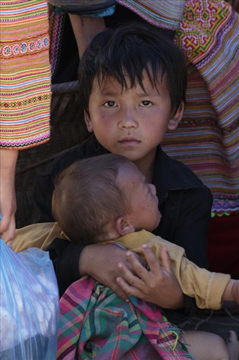 A Hmong Boy trying to calm down his little brother while his parents are busy with selling at the local market in Bac Ha. Responsibility comes early in the remote villages of Northern Vietnam, Family is everything.