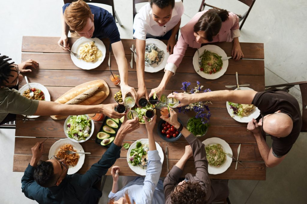 a group of friends gathering around a Thanksgiving table, toasting.