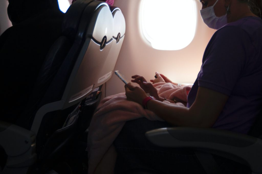 a woman wearing a mask with a baby in her lap on an airplane