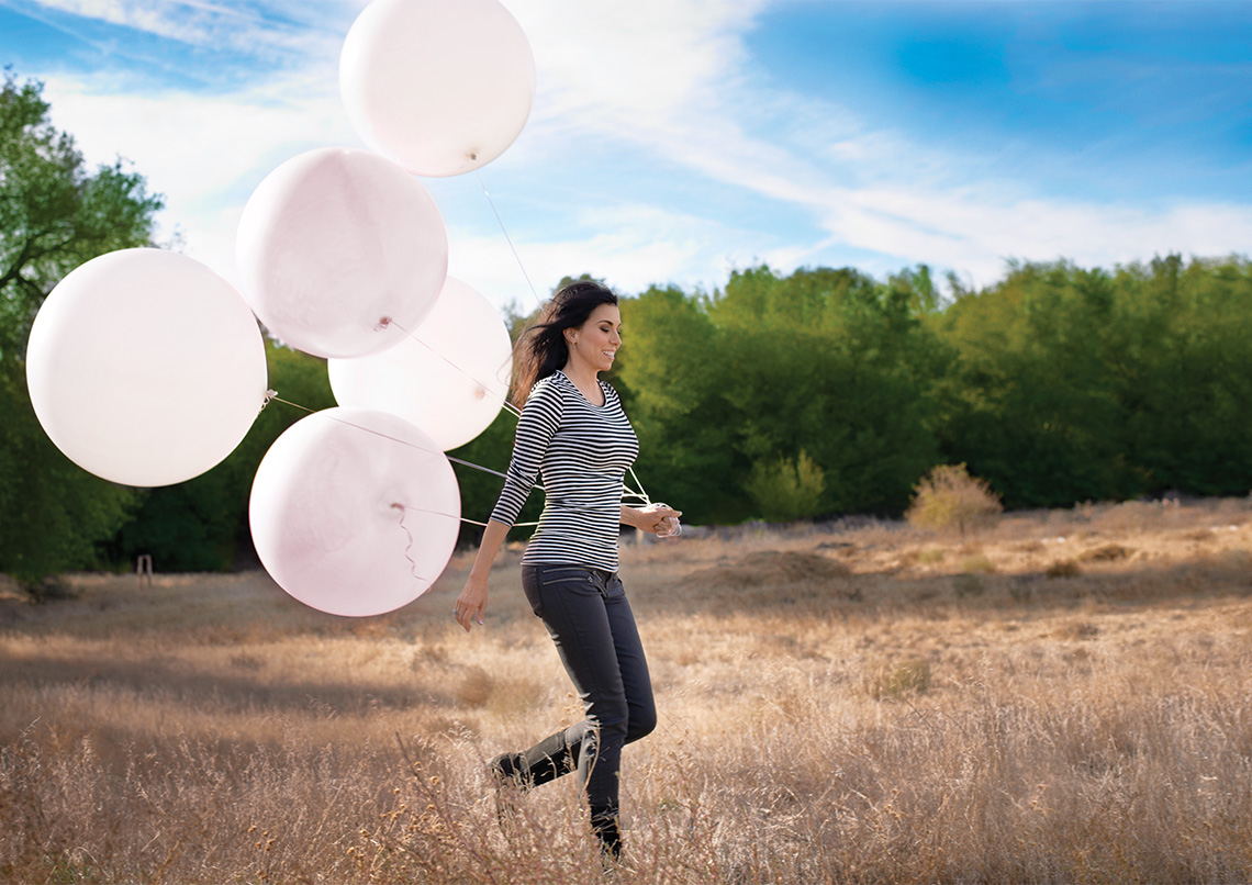 woman running across field with balloons