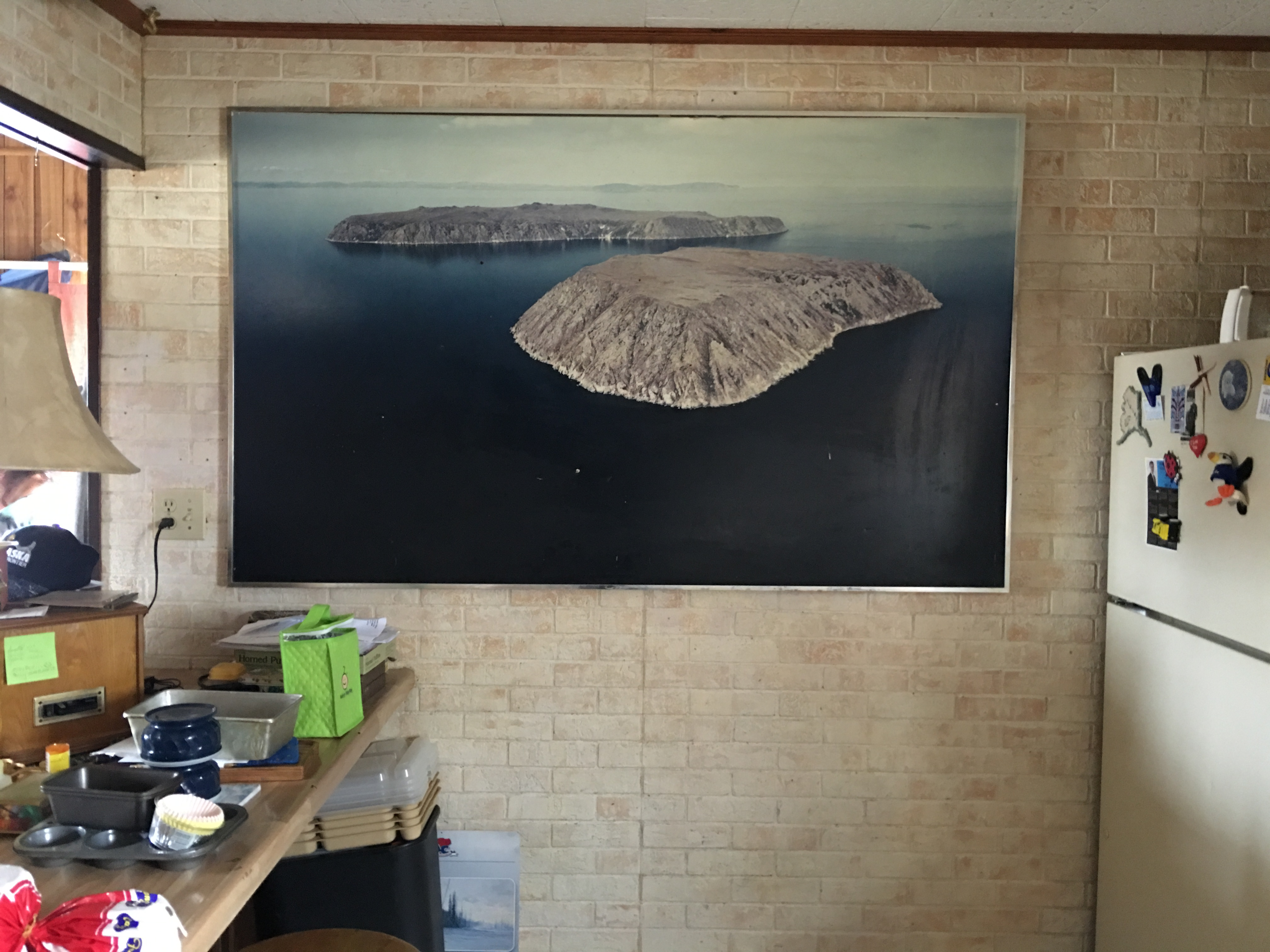 A photo of the Diomede Islands hangs over the kitchen of Etta Tall's home in Nome. Tall, born on Little Diomede, hoped to find relatives from Big Diomede during a two-week voyage through Chukotka in June and July of 2016. (Kirsten Swann / Alaska Dispatch News)