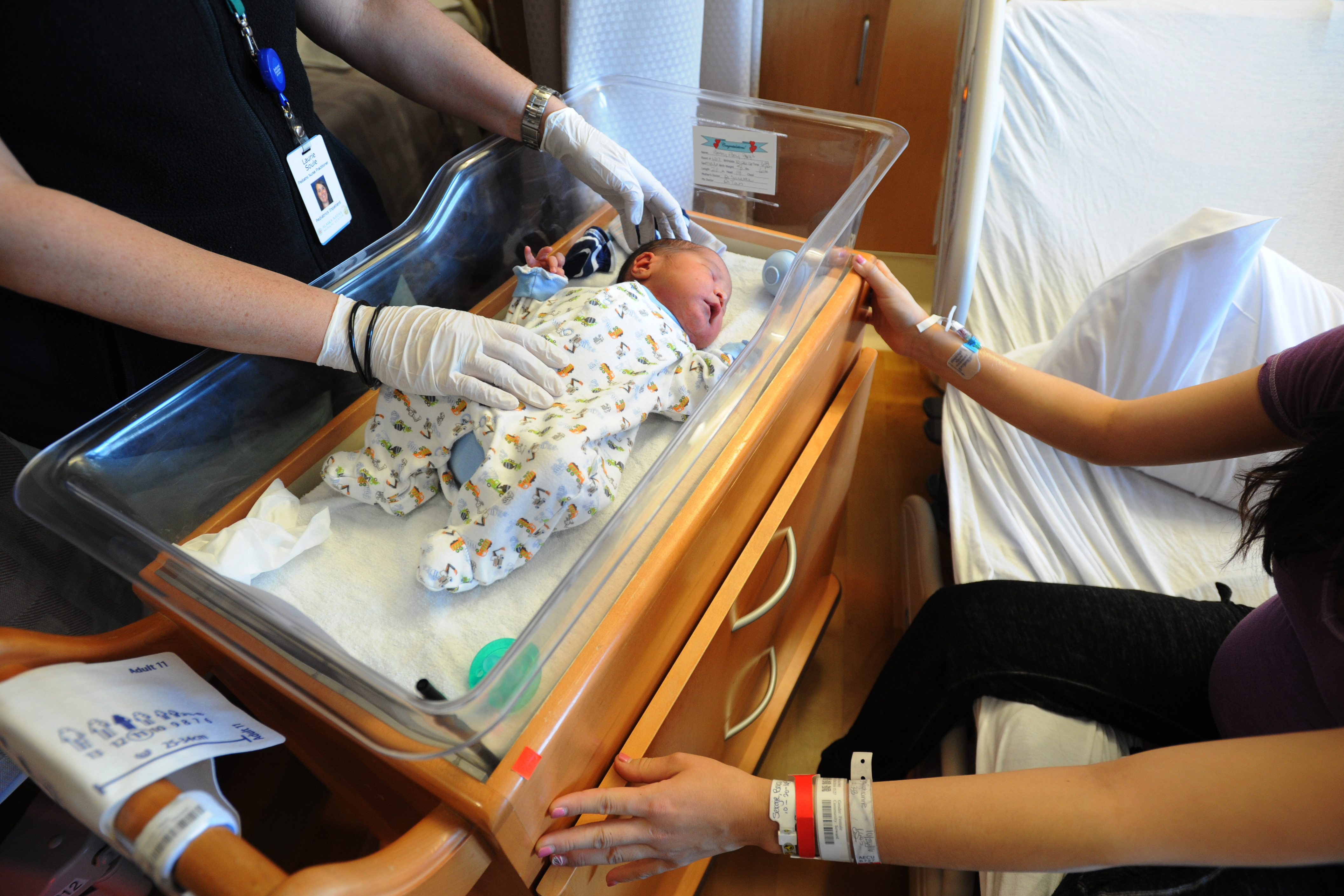 Newborn Ashton Sergie is tended to by nurse practitioner Laurie Soule, left, and mom Sophianne Sergie on Thursday, Oct. 27, 2016, in Family Birthing Services at the Alaska Native Medical Center. Ashton was set to have a blood sample taken later in the day for screening for CPT1A Arctic variant and other conditions. (Erik Hill / Alaska Dispatch News)