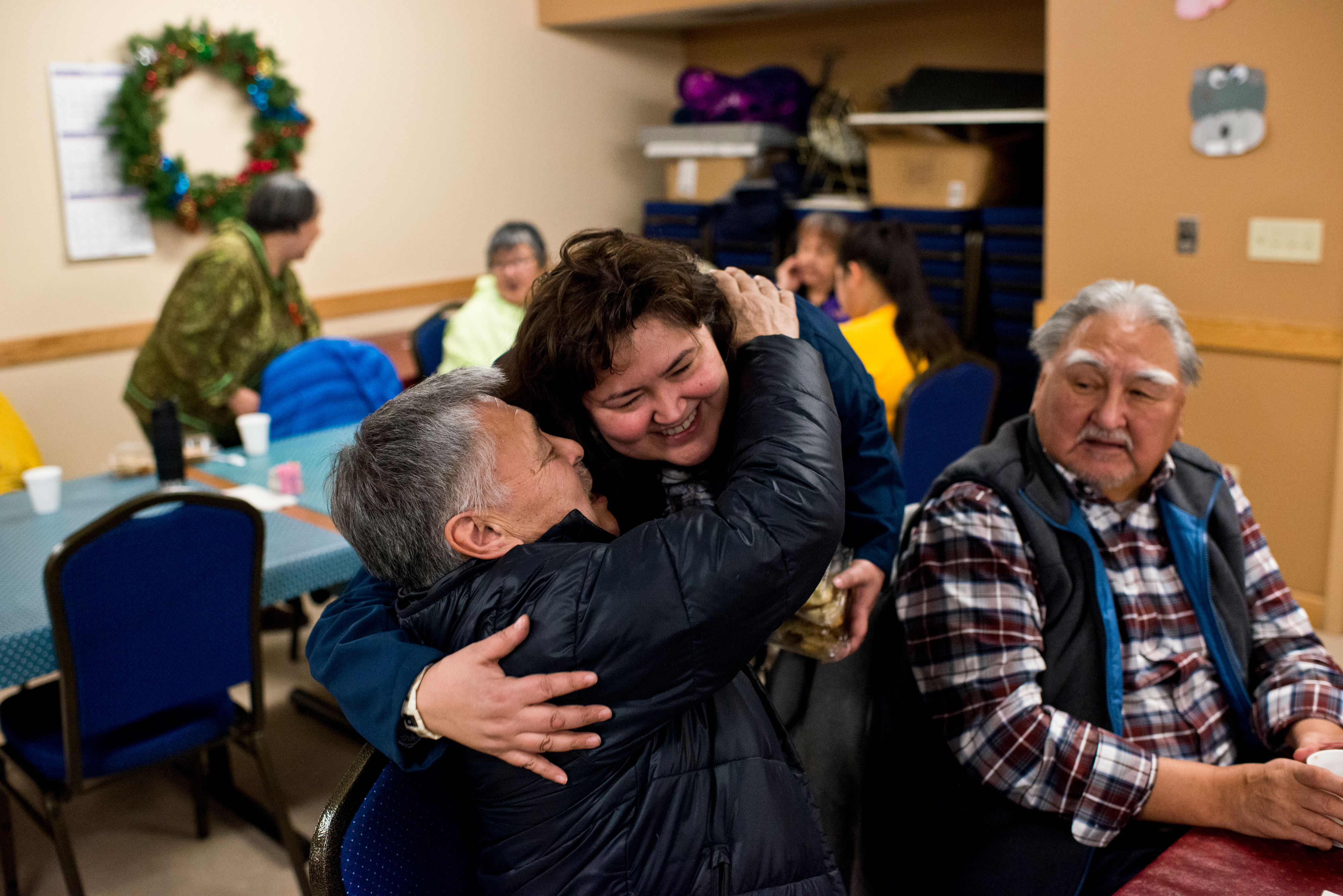 """Arnold Brower gets a hug from Susan Hope during a holiday dinner at the North Slope Borough Senior Center. Brower says he's open to the name change as it was approved by voters, and that people will accept it in time. """"I know it won by a small margin, but that's what politics is,"""" he said. Voters approved changing the name of the city of Barrow to Utqiagvik in October, a change which went into effect on December 1. In Alaska's northernmost city, however, residents remain divided about whether they name should've changed at all, whether the process was hurried, and whether the Utqiagvik is even the proper Inupiaq place name. Photographed on Monday, December 12, 2016. (Marc Lester / Alaska Dispatch News)"""