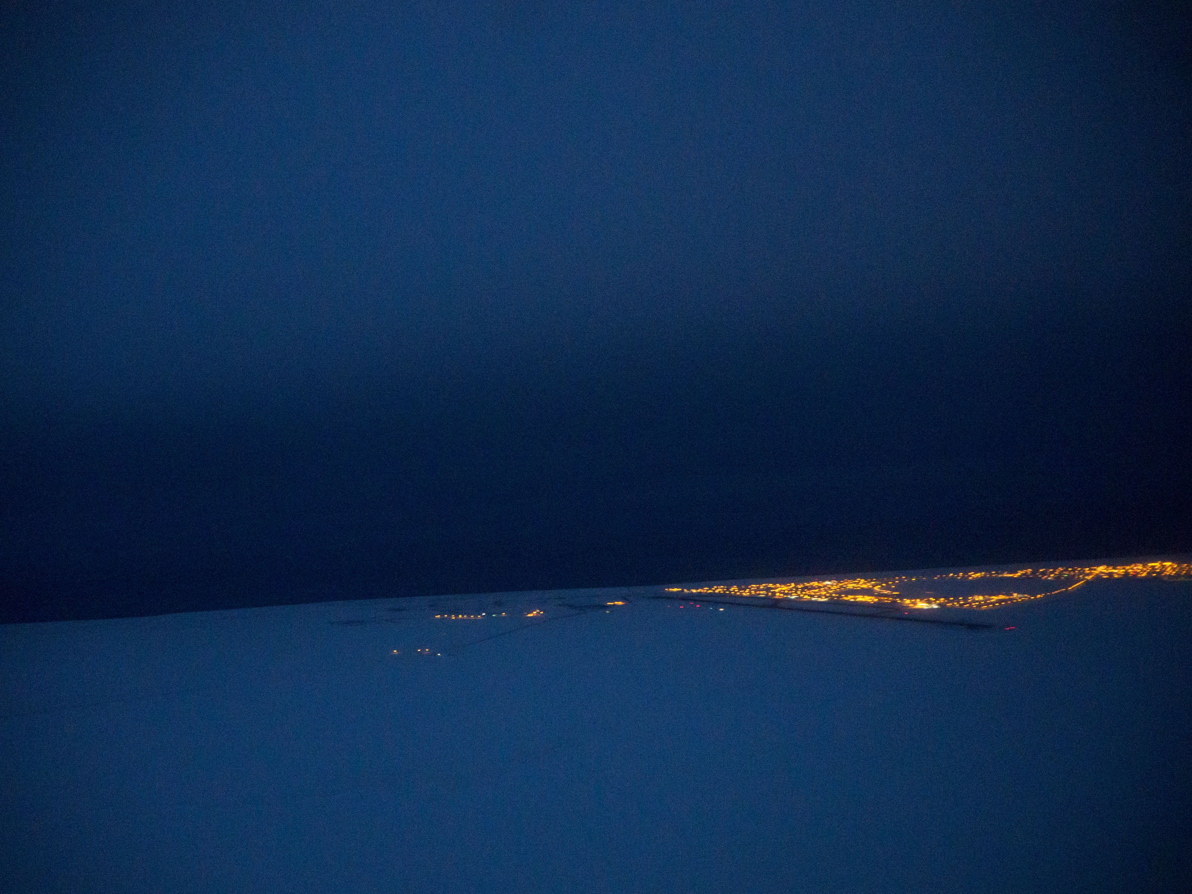 Lights of Utqiagvik are visible from a midday flight out of town. When someone is lost or stranded in the wild lands within 25 miles of Utqiagvik, volunteers from Barrow Search and Rescue often take they lead in retrieving them. The group also has helped map camps and cabins in the region, stake trails between village and provide emergency beacons for travelers. Photographed on Thursday, December 15, 2016. (Marc Lester / Alaska Dispatch News)