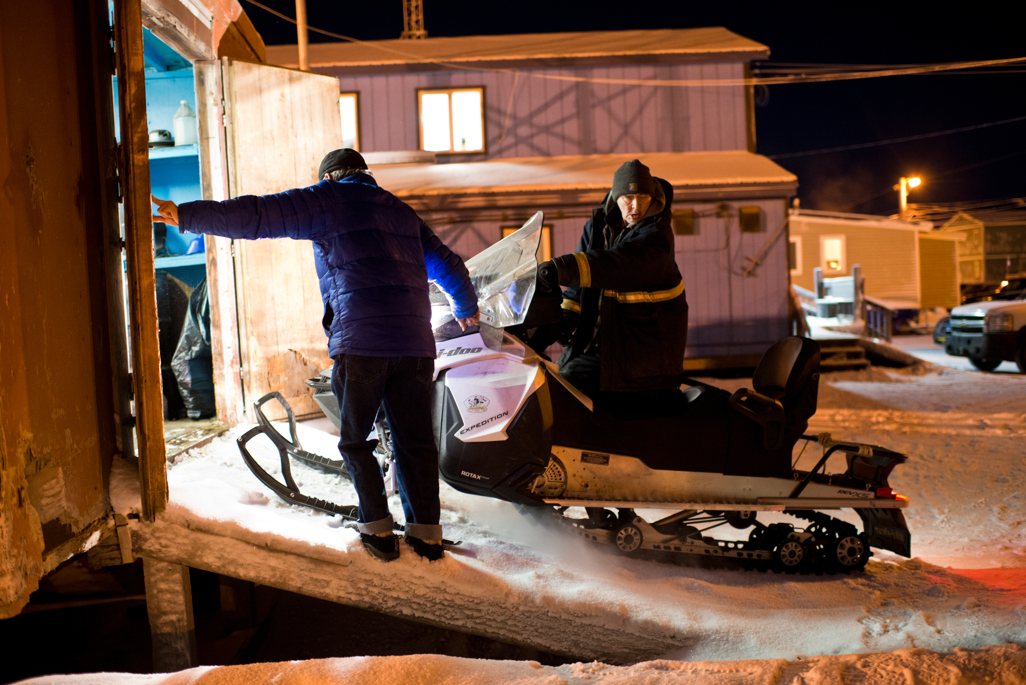 Patrick Brower departs the Barrow Searc and Rescue headquarters to assist a group of four people whose snow machines broke down while on a hunting trip. Johnny Adams holds the door at left. When someone is lost or stranded in the wild lands within 25 miles of Utqiagvik, volunteers from Barrow Search and Rescue often take they lead in retrieving them. The group also has helped map camps and cabins in the region, stake trails between village and provide emergency beacons for travelers. Photographed on Tuesday, December 13, 2016. (Marc Lester / Alaska Dispatch News)