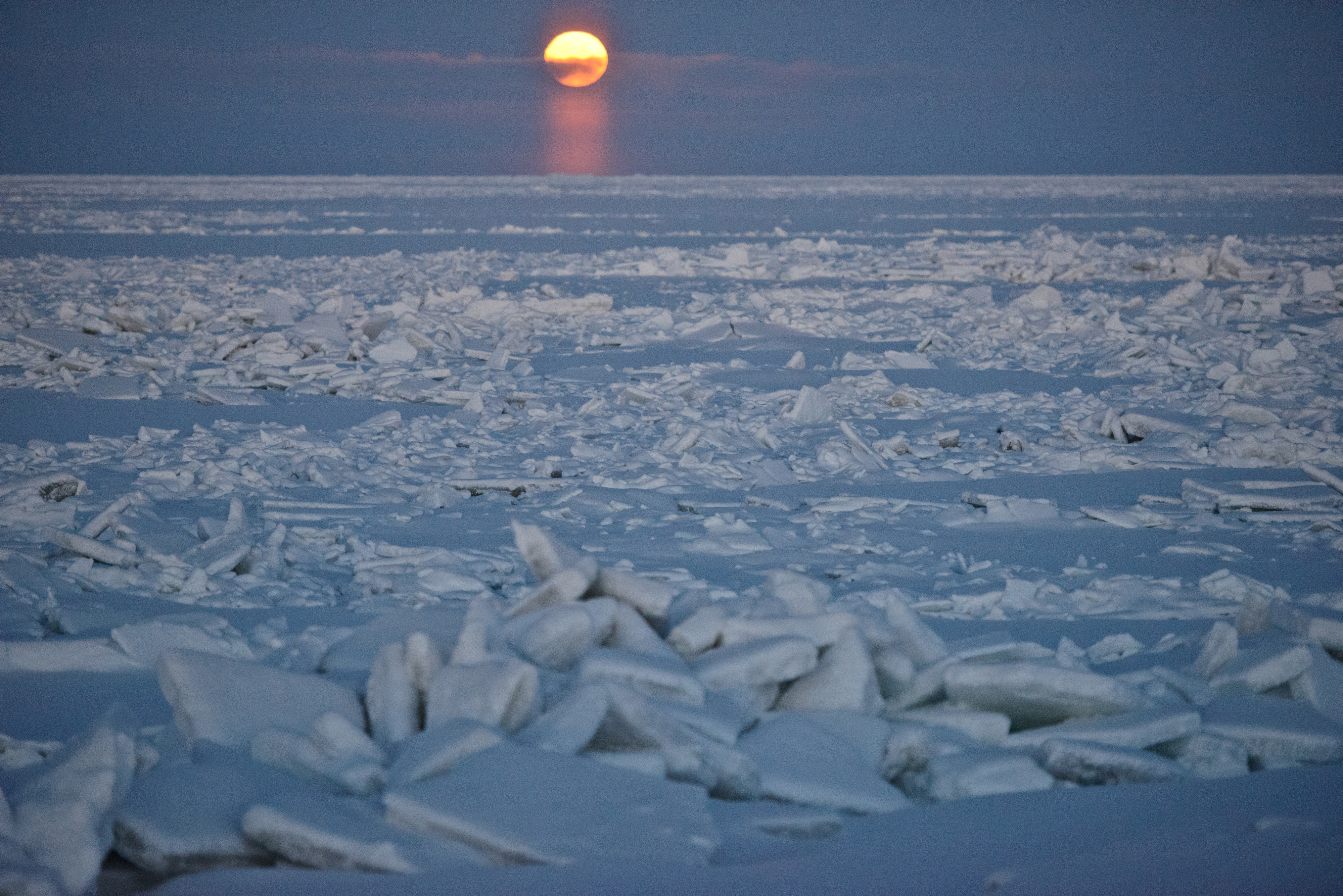 The moon is visible over ice offshore from a road a few miles northeast of Utqiagvik on Tuesday, December 13, 2016. (Marc Lester / Alaska Dispatch News)
