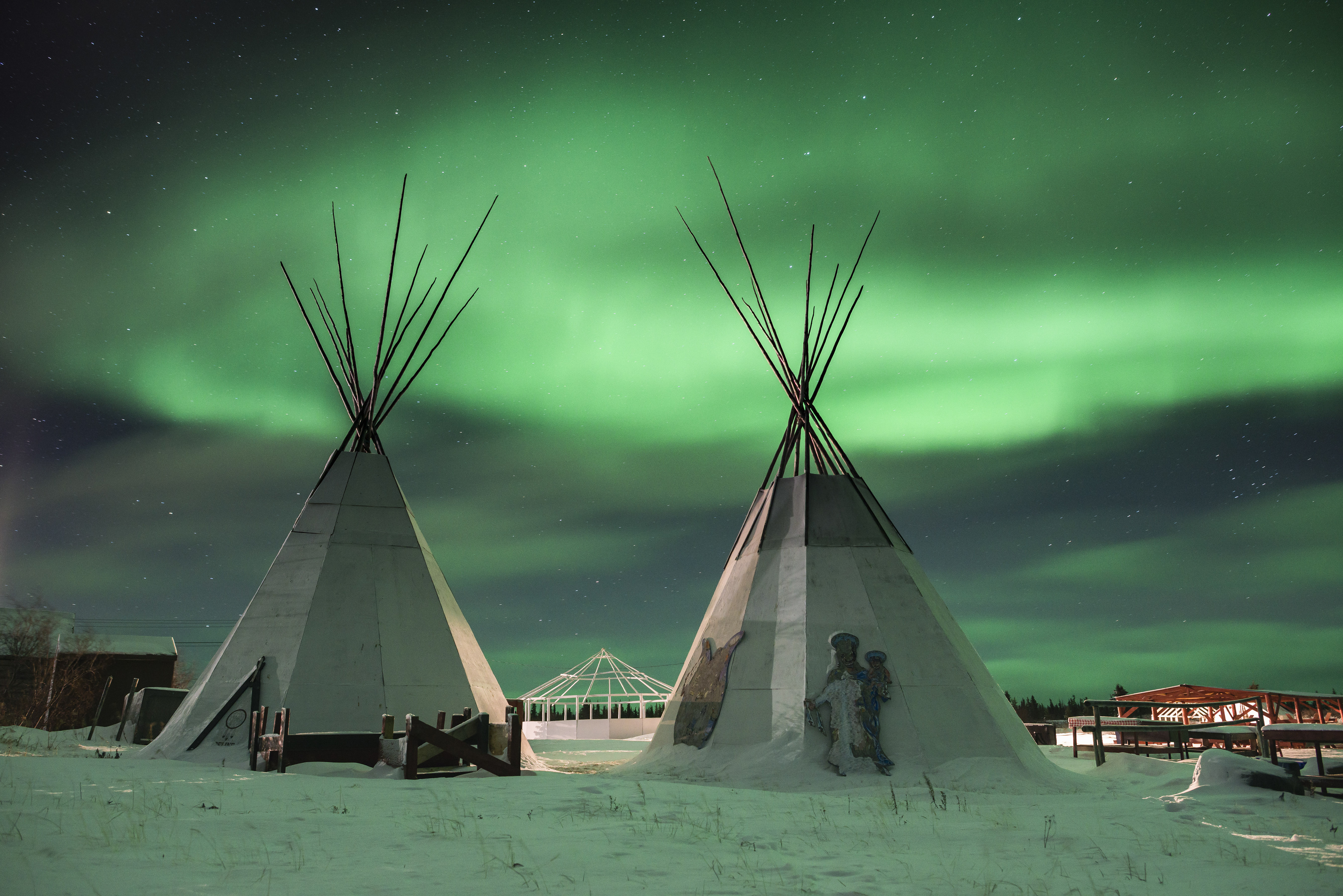 The northern lights illuminate lodges used for smoking fish and drying meat  in Deline, a