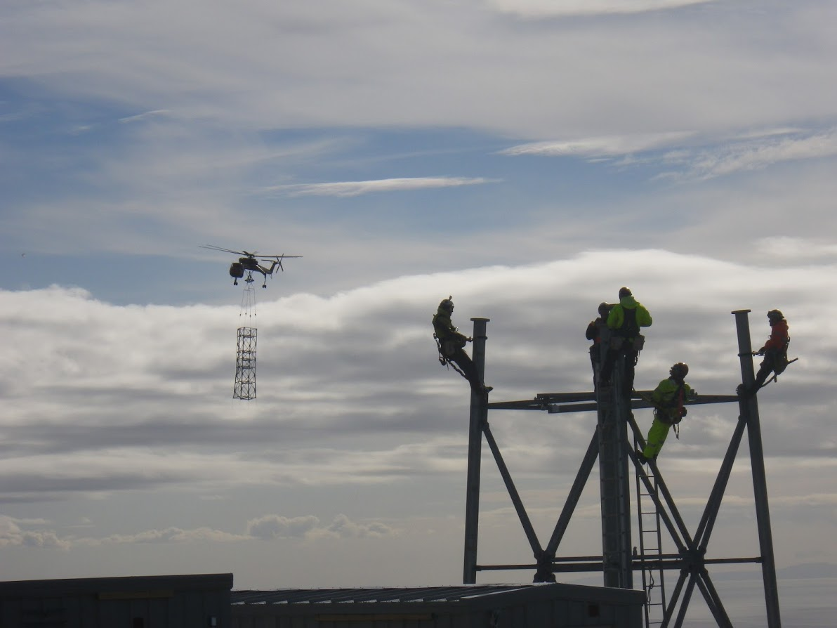 Some TERRA towers are more than 300 ft tall. Sections of tower are flown in to remote regions by helicopter. TERRA construction crews, pictured here, rely helicopters to assist in placement of the tower sections. (GCI photo)