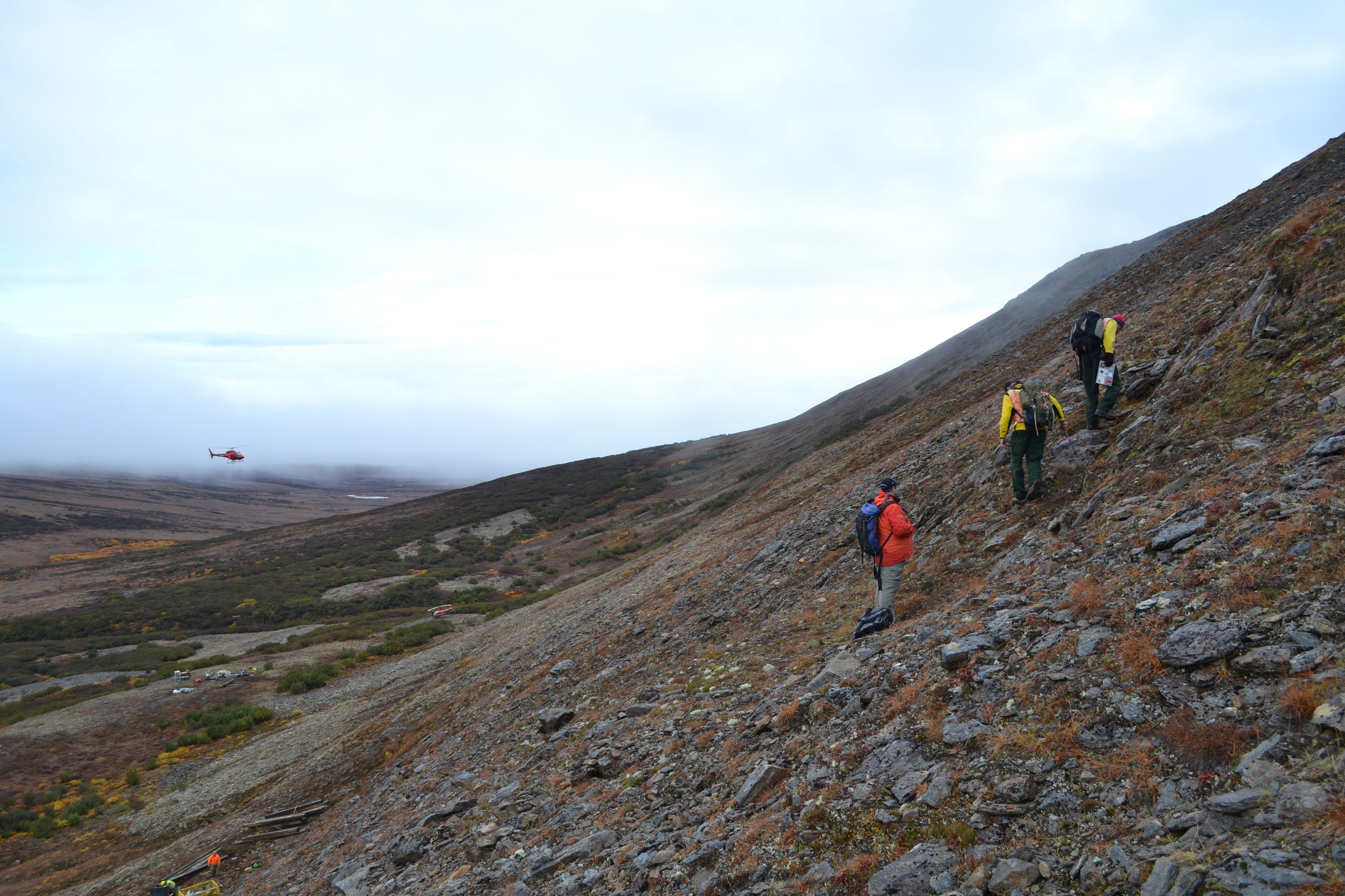 Field crews work on setting up the drilling program at the Graphite Creek project, while BLM geologists inspect a graphite lens outcrop above the drill site. Graphite One Resources' mine prospect, the Graphite Creek project, is near Nome. (Dave Hembree / Graphite One (Alaska) Inc)
