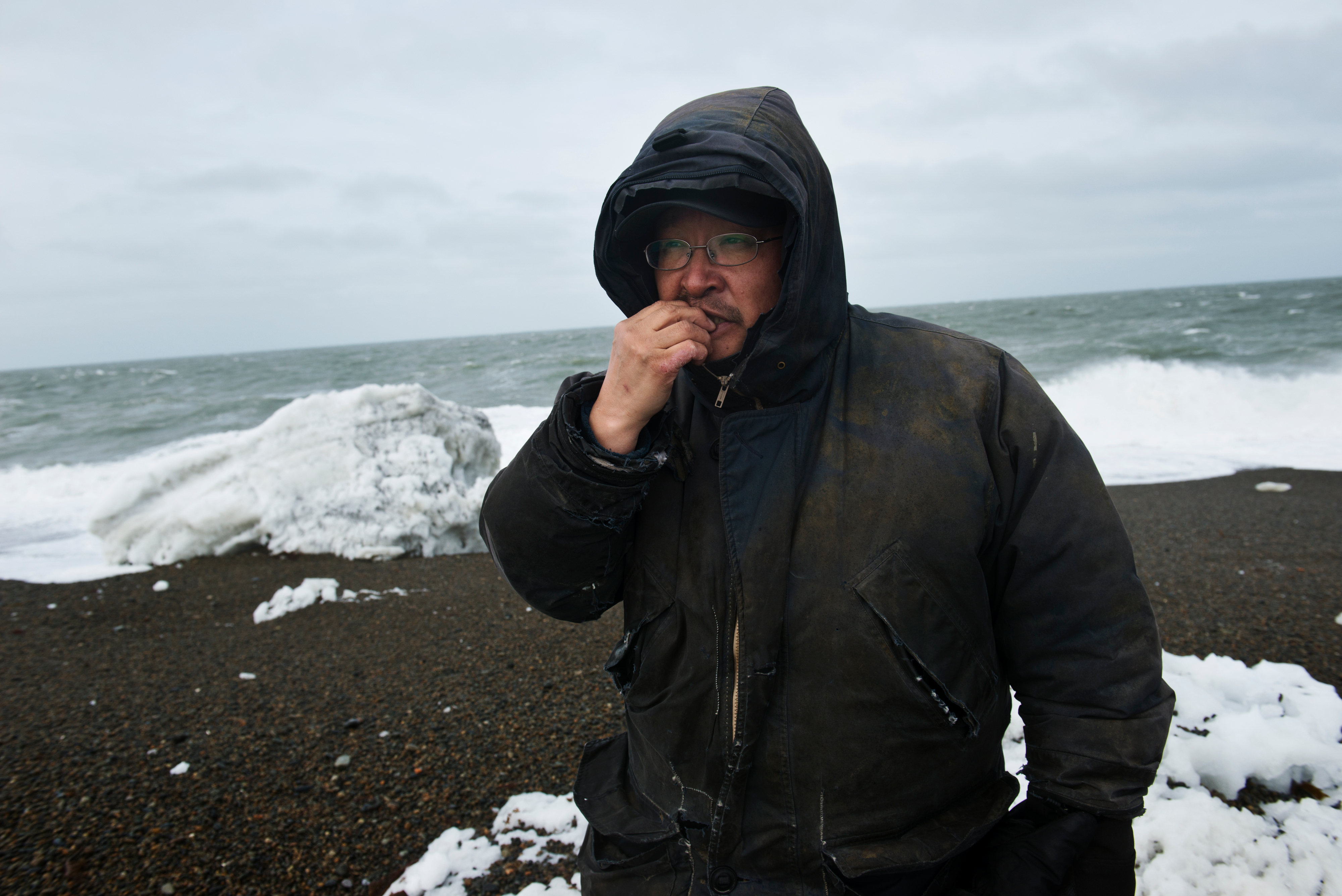 Edmond Apassingok takes a bite of kemkeghnak, one of several tunicates that wash ashore that many residents there eat. Photographed on April 24, 2017. (Marc Lester / Alaska Dispatch News)