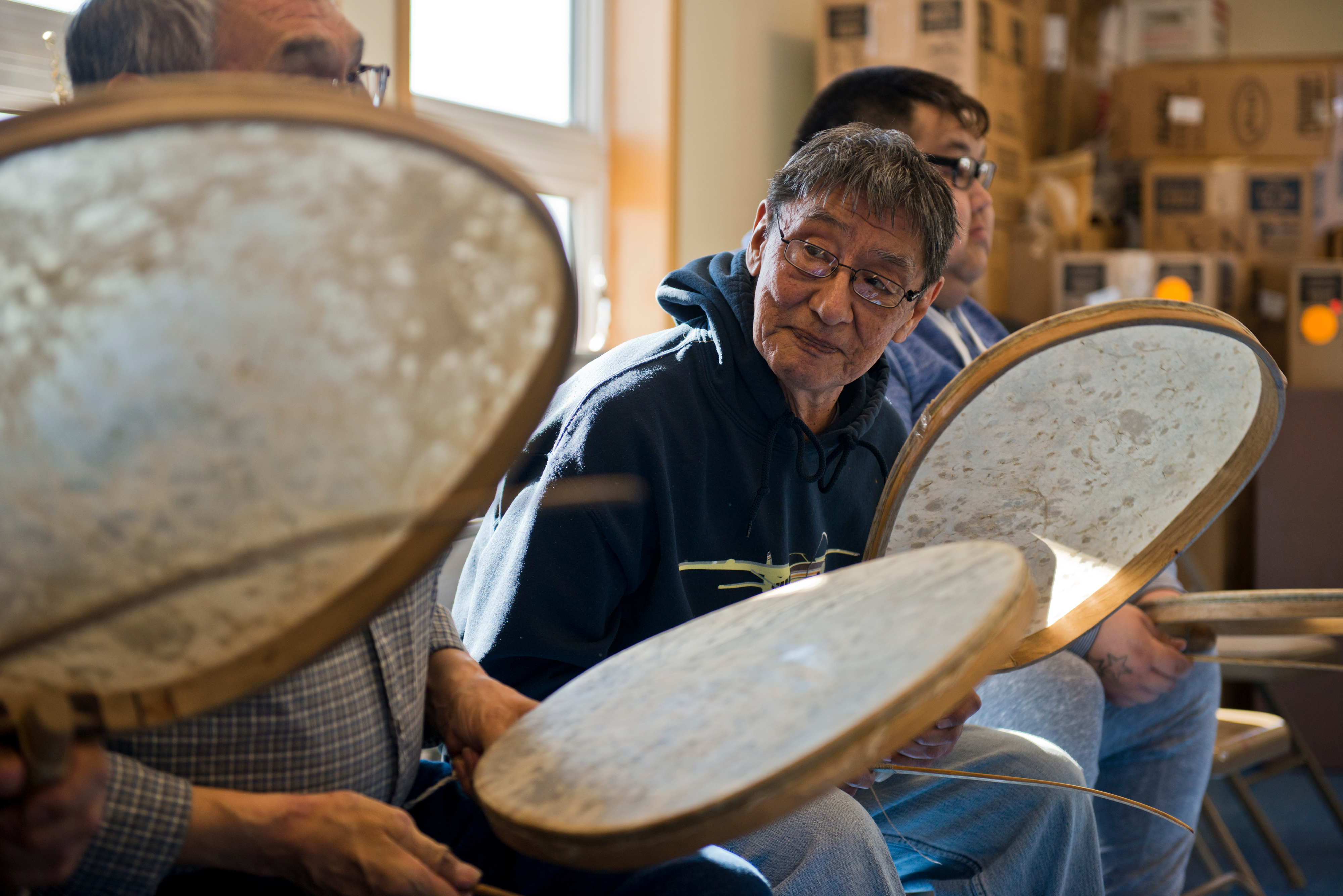 George Noongwook drums with other men at an event in the Native Village of Savoonga building on April 20, 2017. The drums are made with the stomach of walrus. (Marc Lester / Alaska Dispatch News)