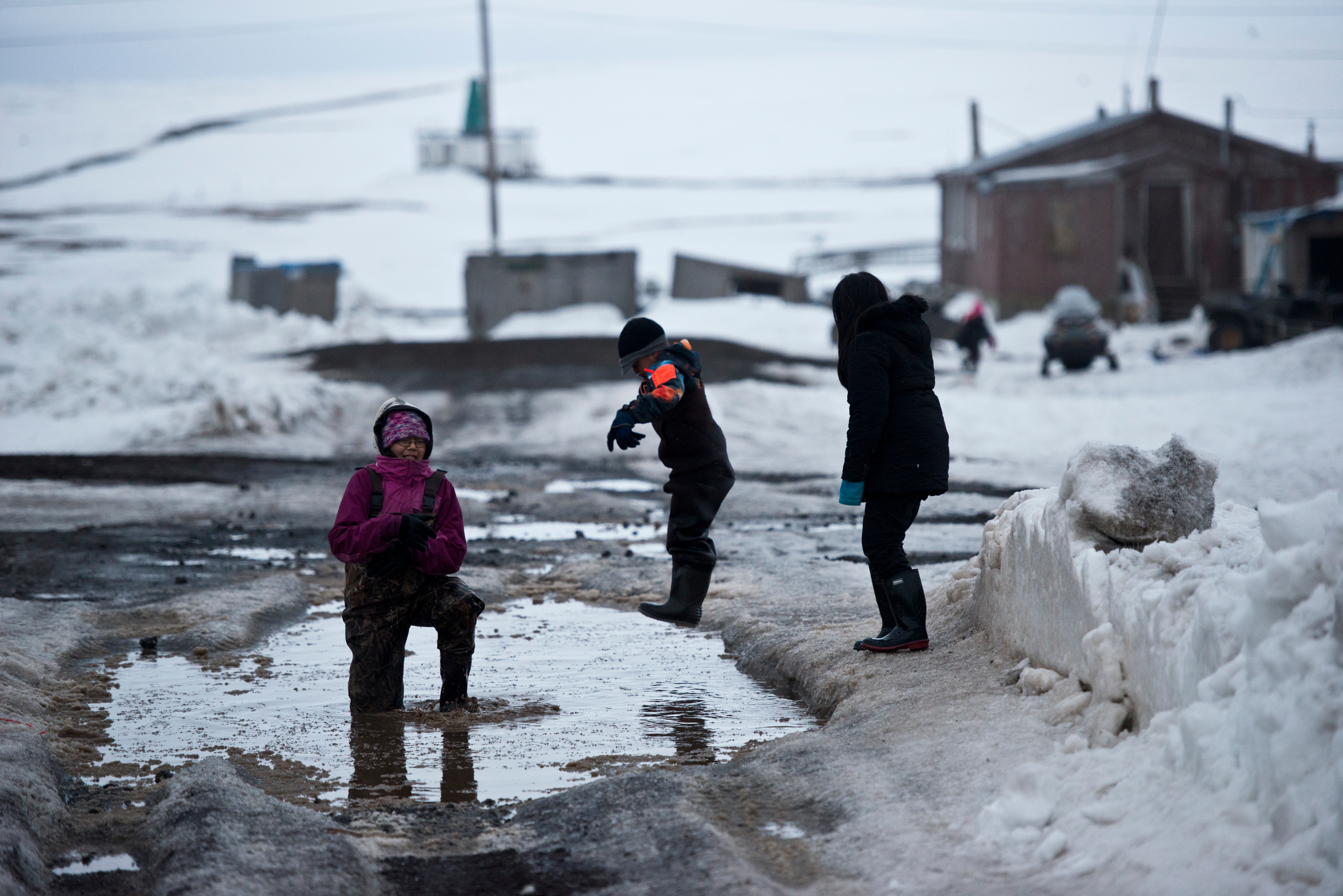 Children play in a deep puddle in Savoonga on April 22, 2017. (Marc Lester / Alaska Dispatch News)