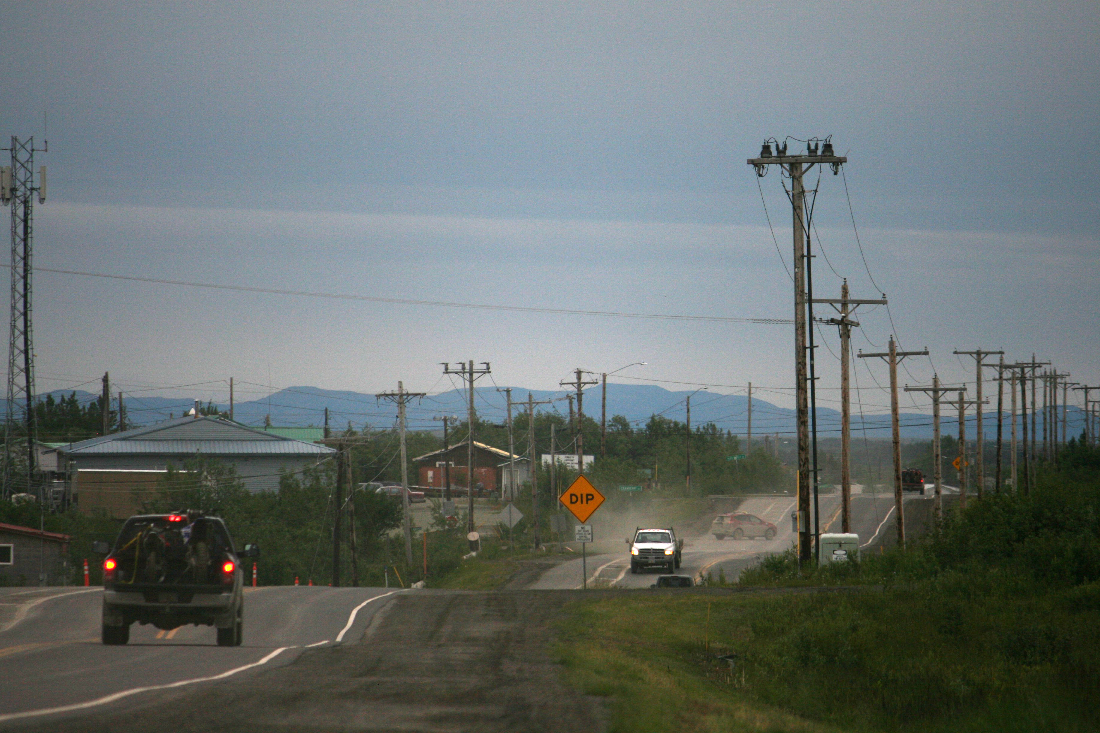 Chief Eddie Hoffman Highway, seen on June 28, 2017, is the main thoroughfare in Bethel, and one of few paved roads. It has become a roller coaster of a ride over the past couple of years. The state Department of Transporation is studying whether heaves from the thaw-freeze of permafrost is a factor. (Lisa Demer / Alaska Dispatch News)