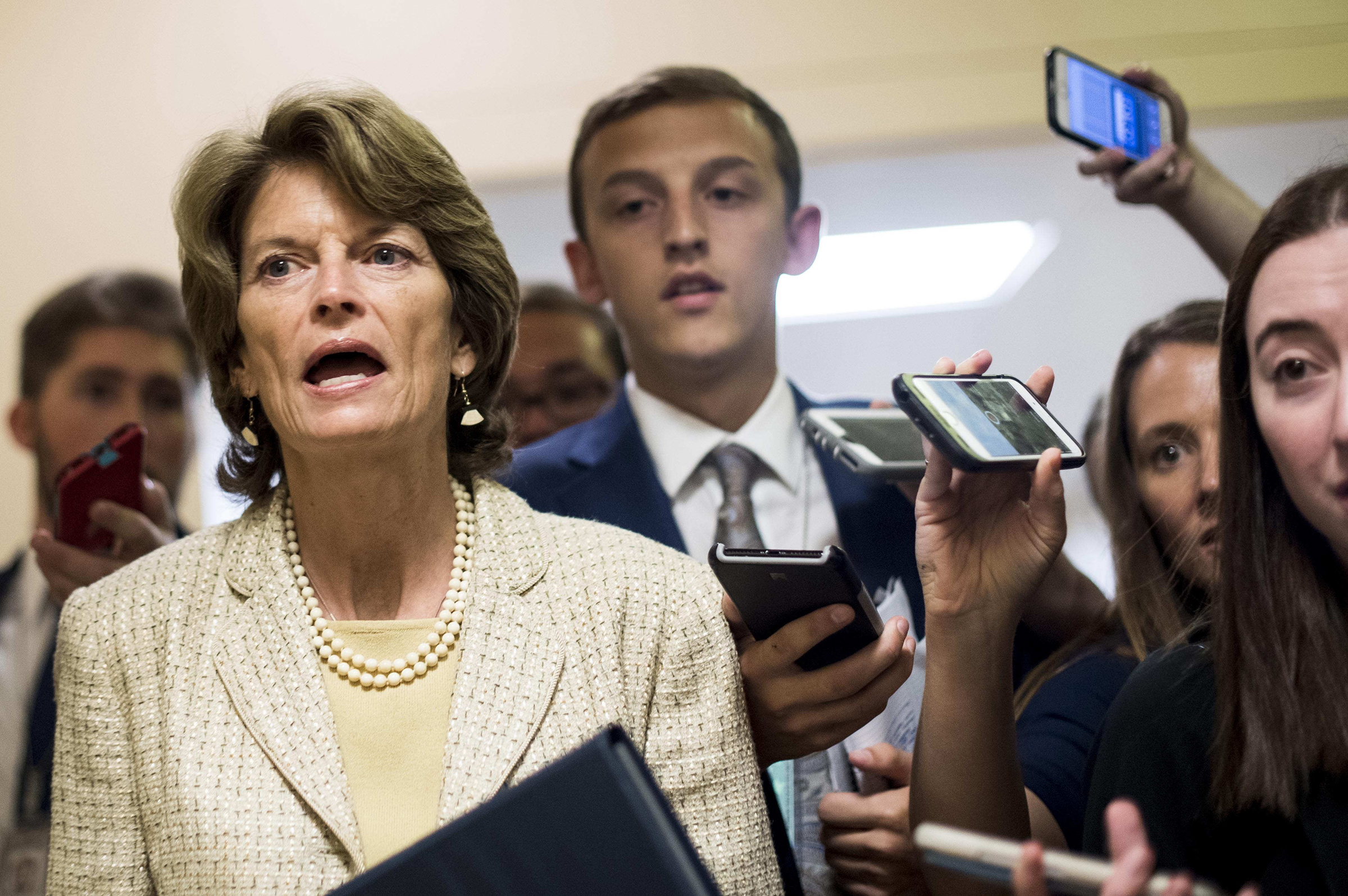 Sen. Lisa Murkowski answers questions from journalists while rushing to votes concerning the Republican version of the health care bill on Capitol Hill on Thursday. (Melina Mara / The Washington Post)