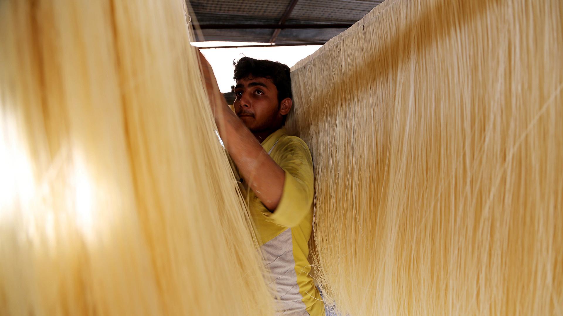 Un vendedor Pakistán organiza los fideos tradicionales con los que los musulmanes celebran Ramadán al caer el sol (AP)