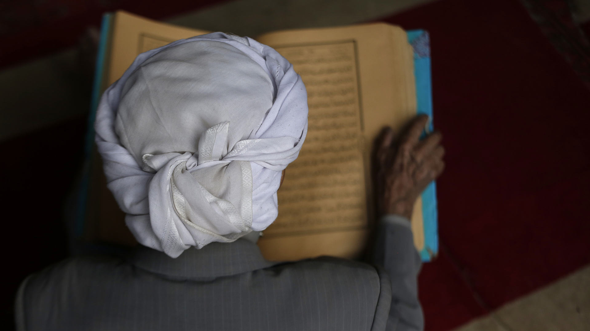 Un hombre lee versos del Corán, el libro sagrado del islam, en el primer día del mes de ayuno del Ramadán en la Gran Mezquita de la ciudad vieja de Sanaa, Yemen (AFP)