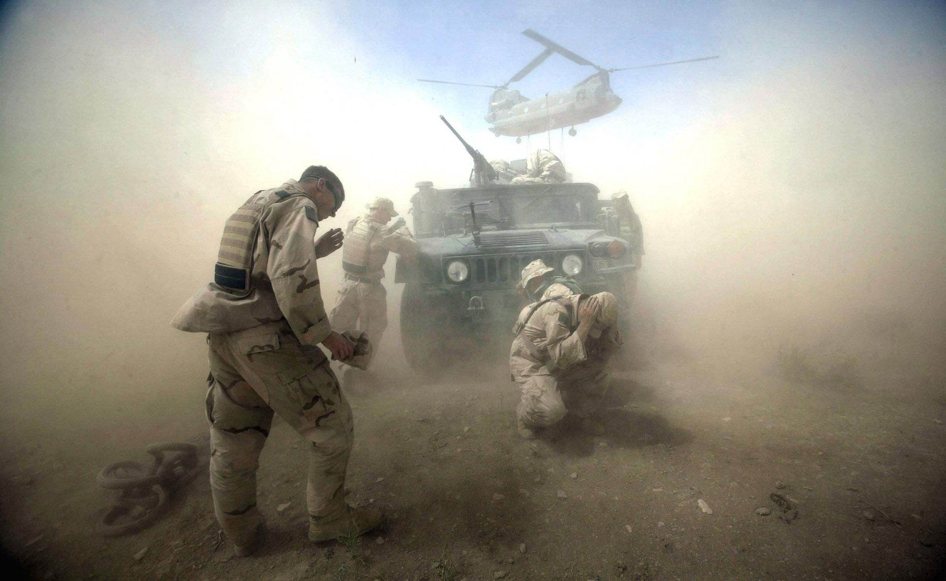 Soldados estadounidenses tratan de luchar contra el incómodo polvo que levantan los rotores del helicóptero Chinook en la provincia de Kadahar, en Afganistán