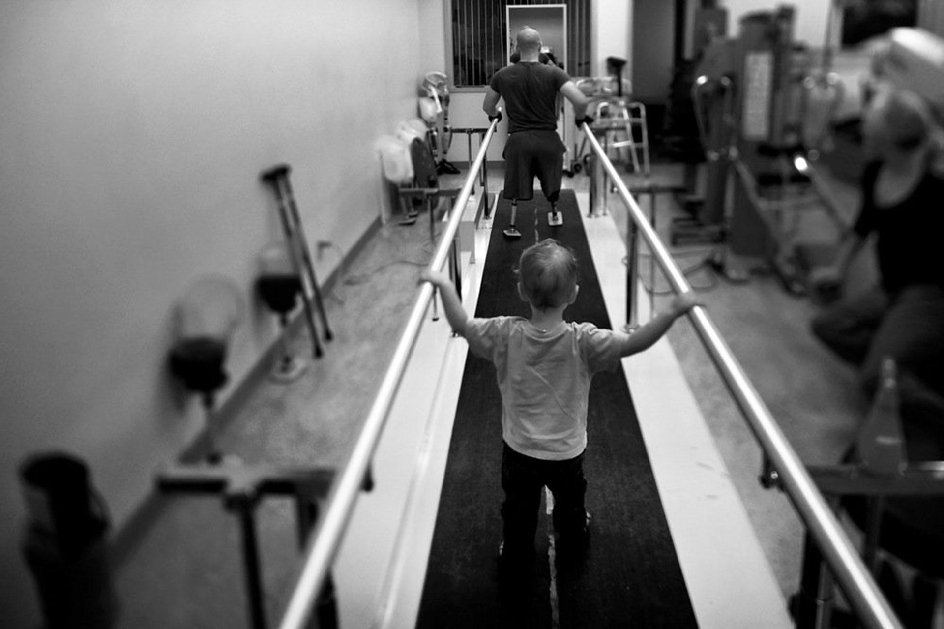En el Centro Naval Médico de San Diego, el marine Jake Romo hace rehabilitación física luego de perder ambas extremidades en Afganistán en 2011. Su pequeño hijo lo acompaña enlarecuperación