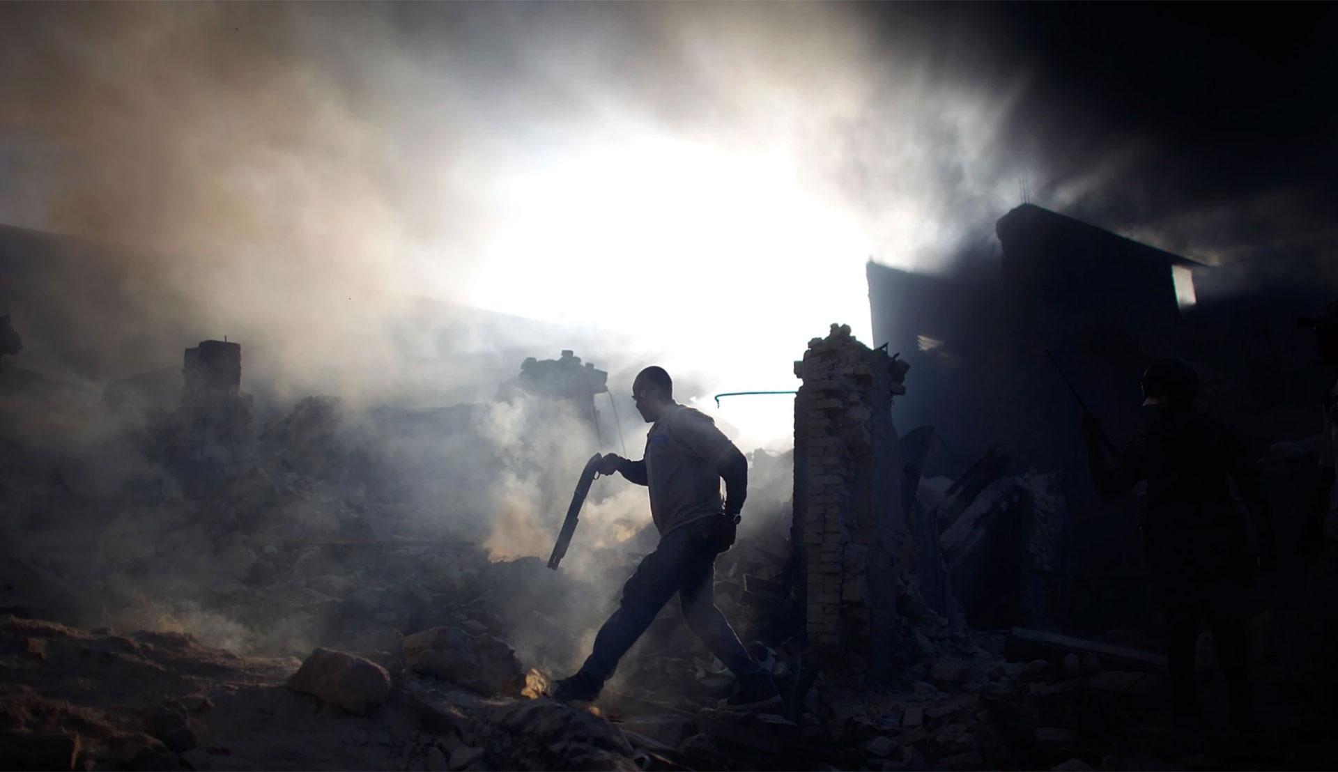 En Puerto Príncipe, David Gilkey capturó este dramático momento: un hombre, entre las ruinas, porta un arma larga. Era el 18 de junio de 2010 y todo era devastación en Haití