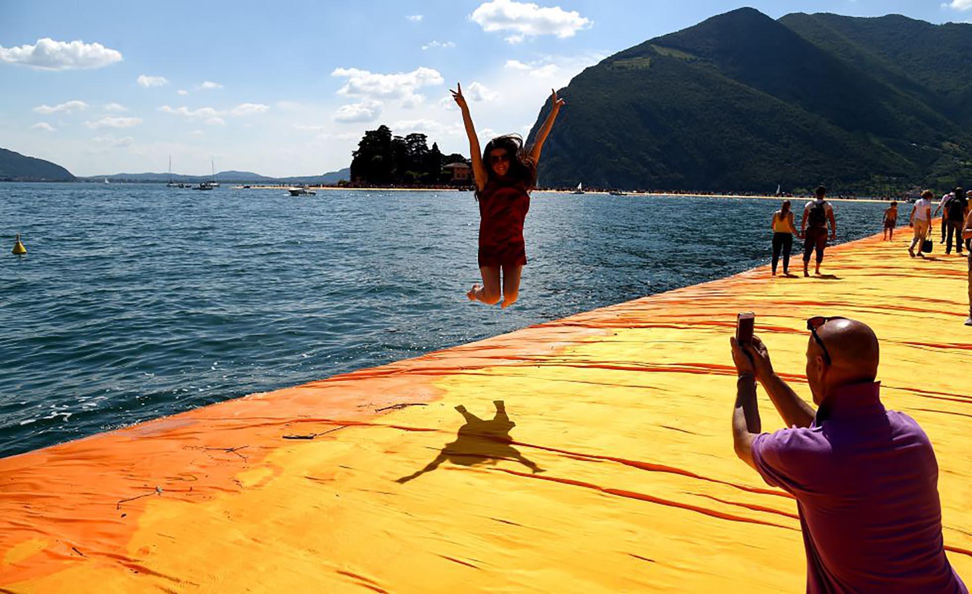 Una visitante de 'Los muelles flotantes', de Christo y Jeanne-Claude, salta sobre la pasarela efímera sobre el lago Iseo, en Italia