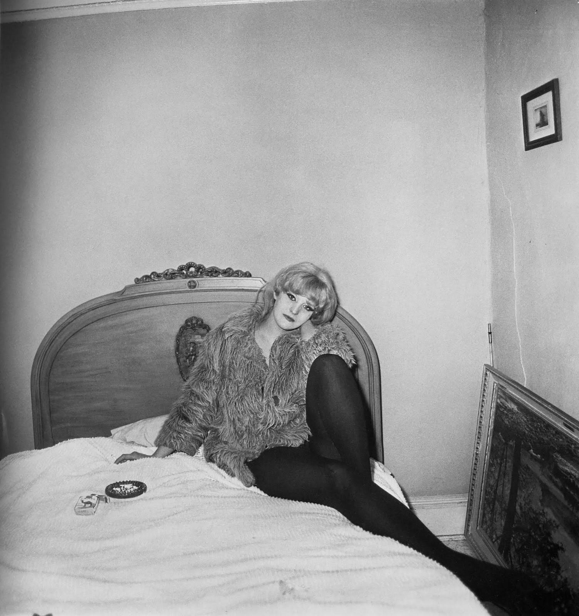 Una chica con abrigo en su cama de Nueva York, 1968.