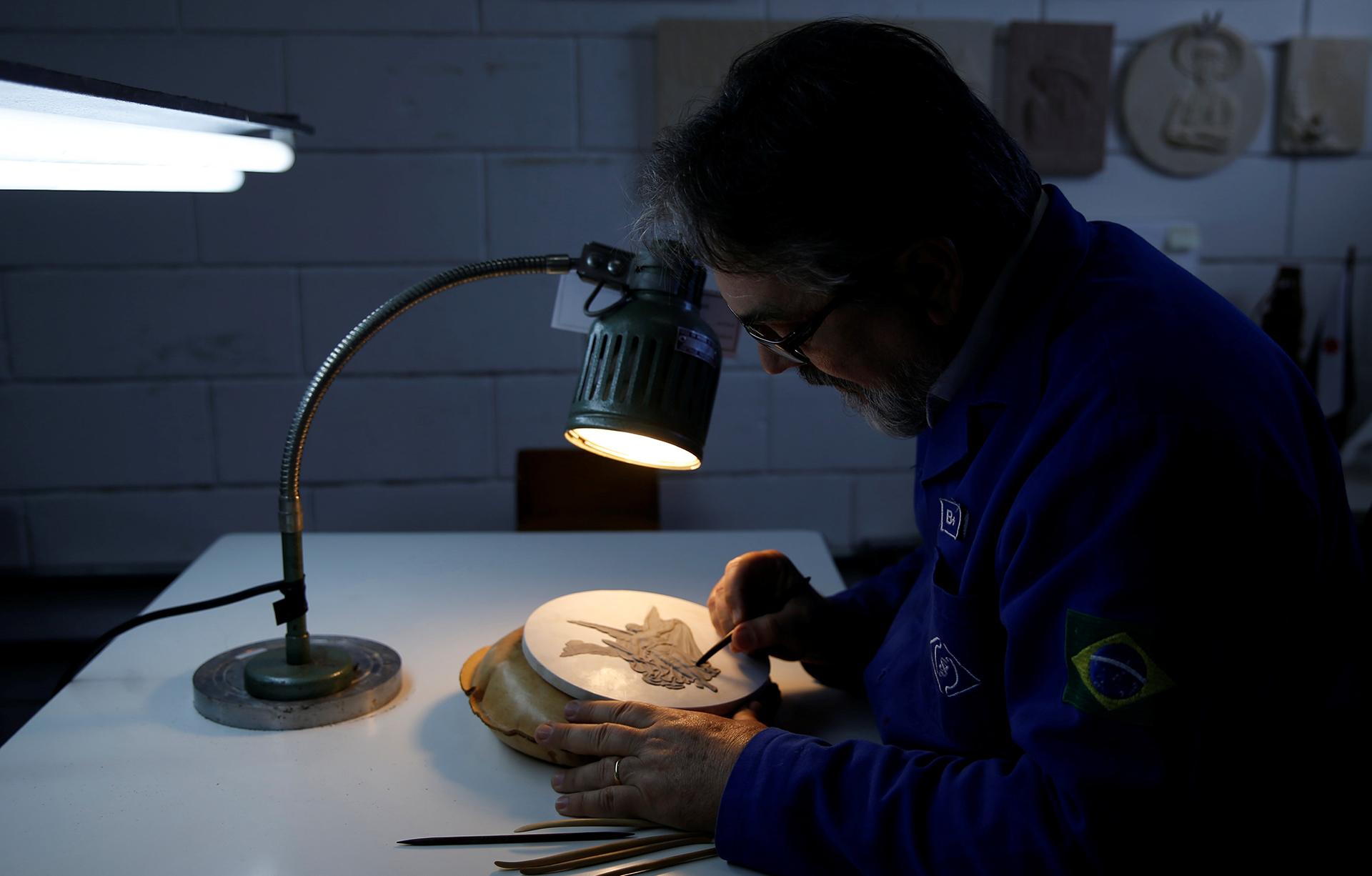 Un artesano trabaja sobre el molde de una medalla en la Casa de la Moneda en Brasil (Reuters)