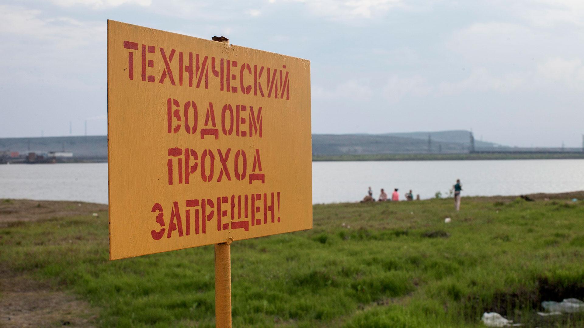 """Las familias se refrescan en las lagunas articiales a pesar del cartel que advierte: """"Aguas técnicas, prohibido el paso""""."""
