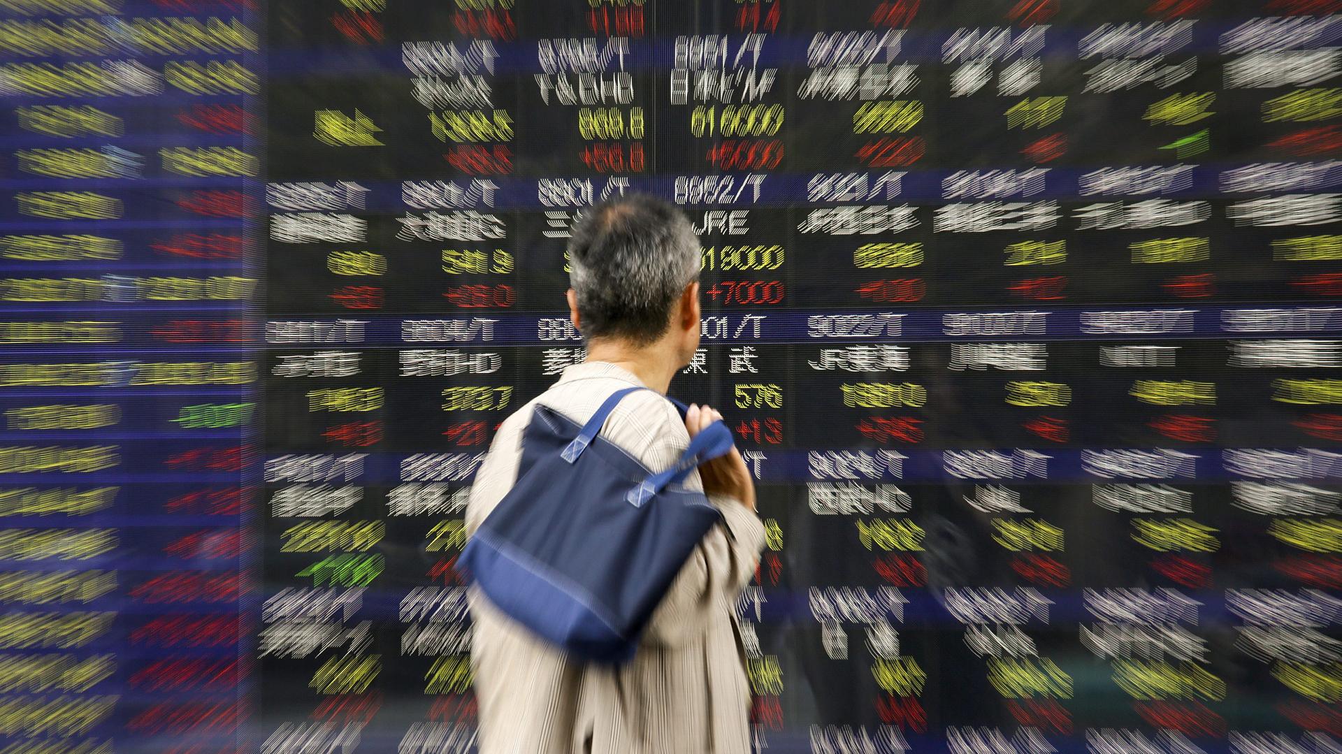 Un peatón observa un panel con la información del cierre del índice de referencia Nikkei (EFE)