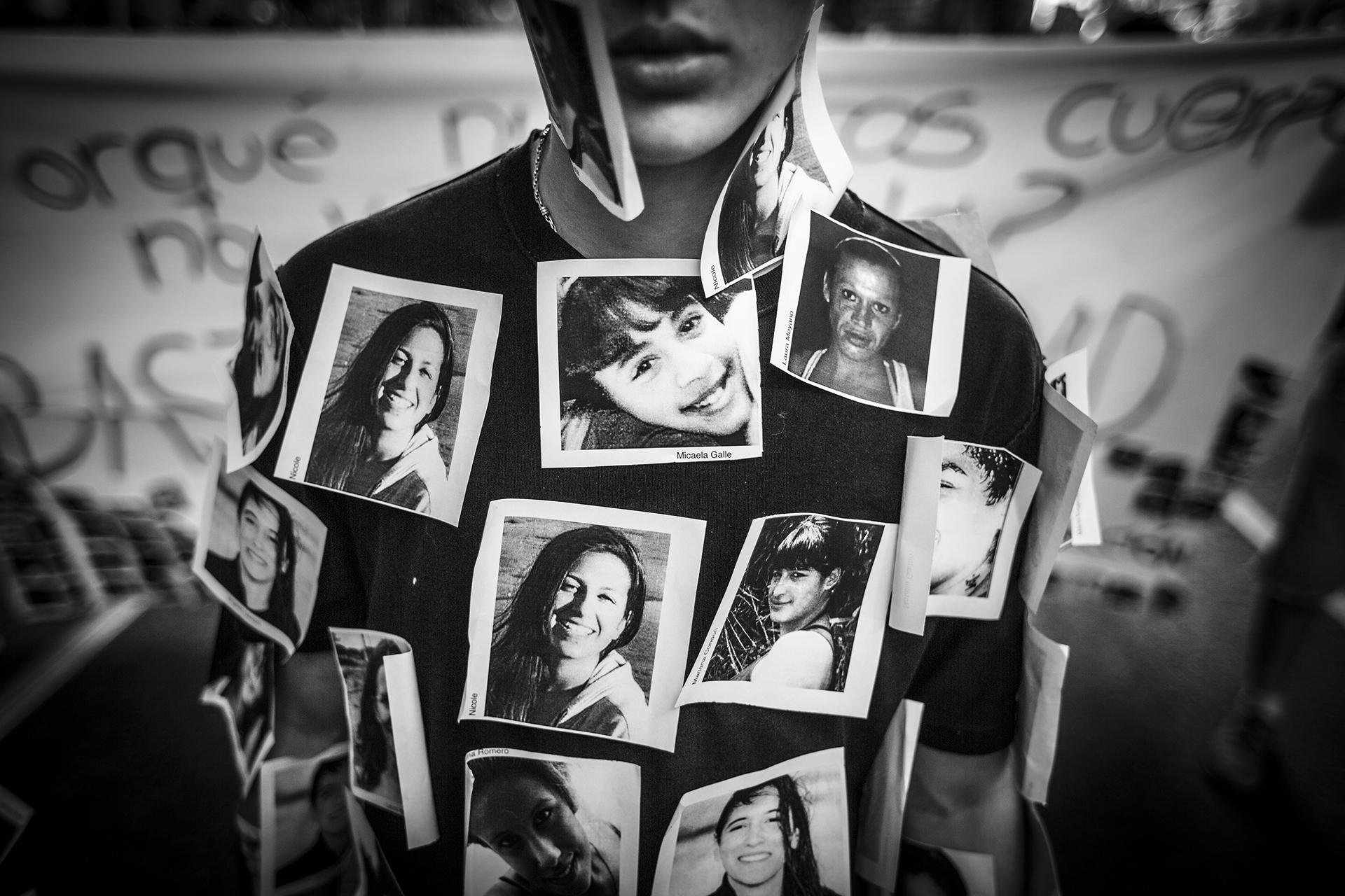 """Un joven realiza una perfomance con fotos de víctimas de violencia de género, durante la marcha """"Ni una menos"""" desde el Congreso Nacional a la Plaza de Mayo (Martín Zabala)"""
