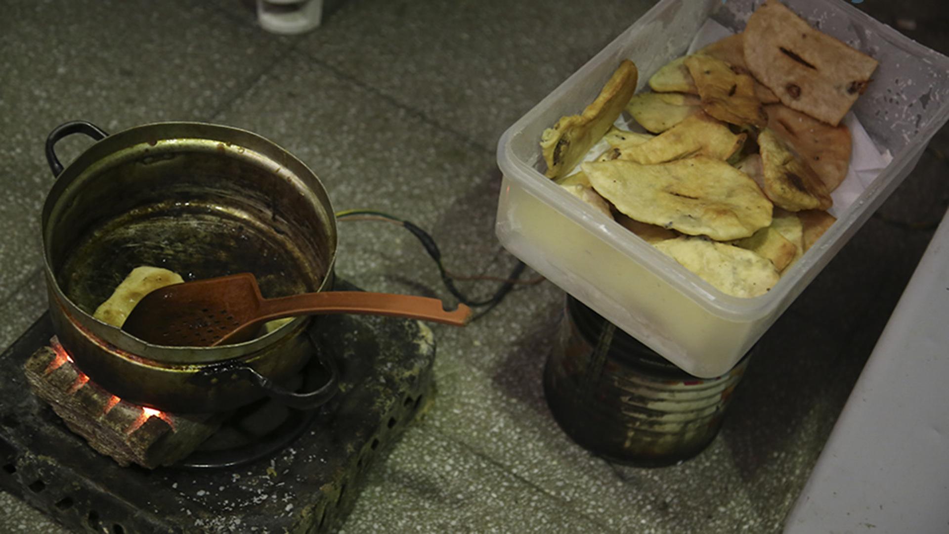 Un detenido improvisa unas batatas fritas en un brasero.