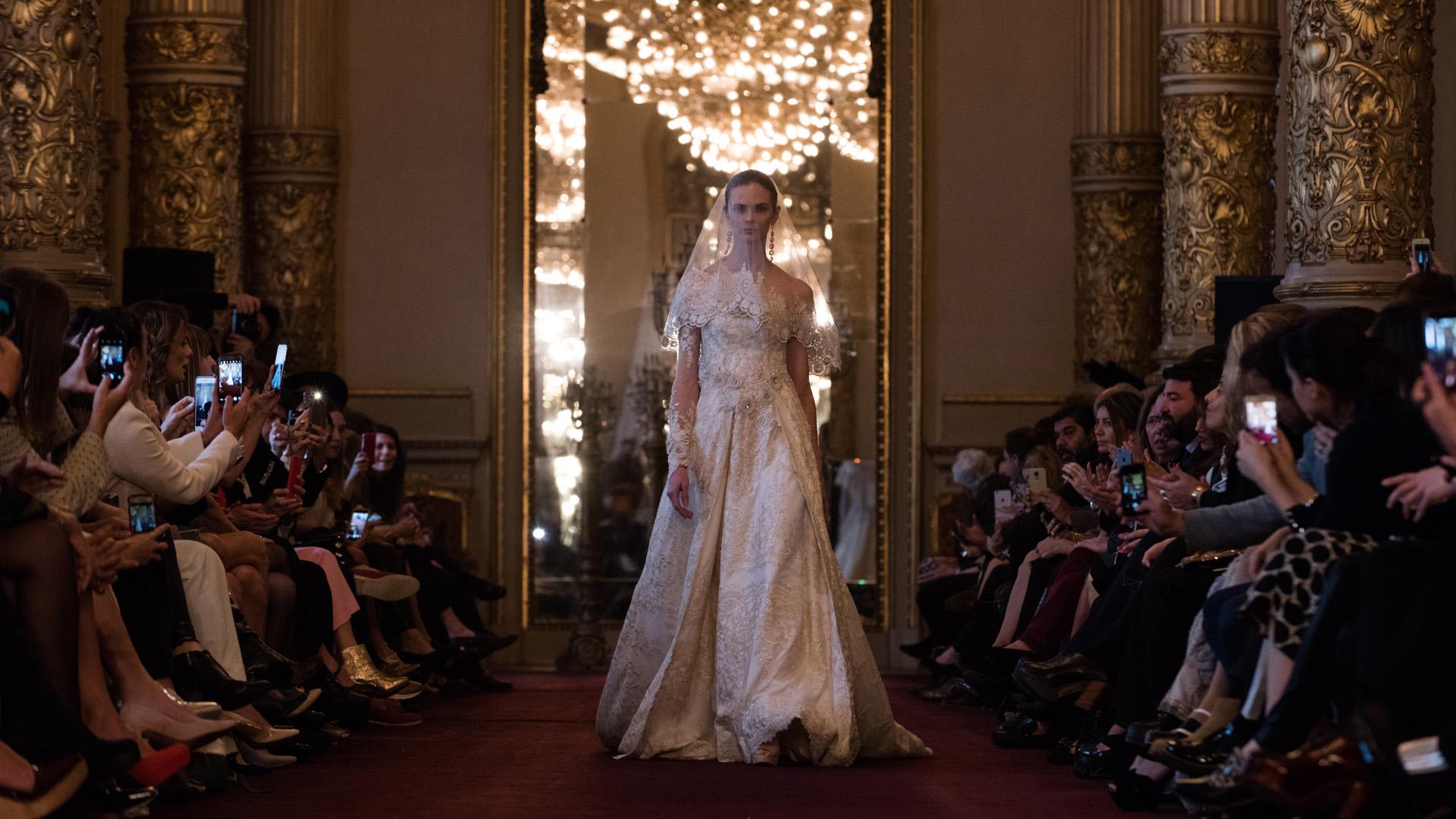 Vestido de novia color marfil, semi-armado en encaje rebrode francés, con escote asimétrico, mangas transparentes y detalles de bordados de flores y strass plata