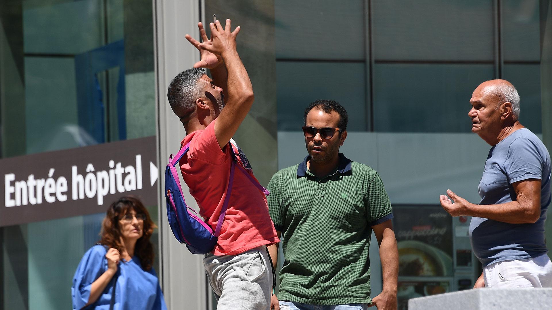 Un hombre exaltado junto a otros dos esperan noticias sobre los heridos en un hospital de Niza (AFP)