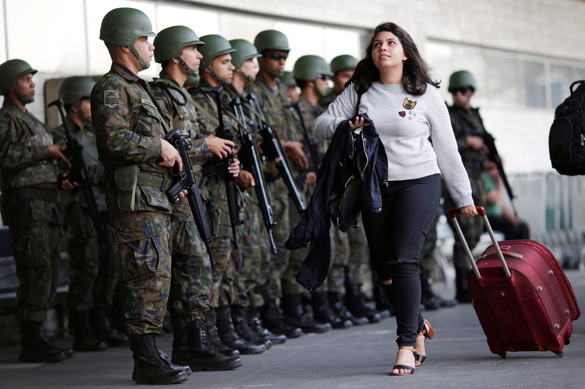 Una pasajera camina delante de los integrantes de la Fuerzas Aéreas de Brasil durante un ensayo en el Aeropuerto Internacional de Galeão (REUTERS)