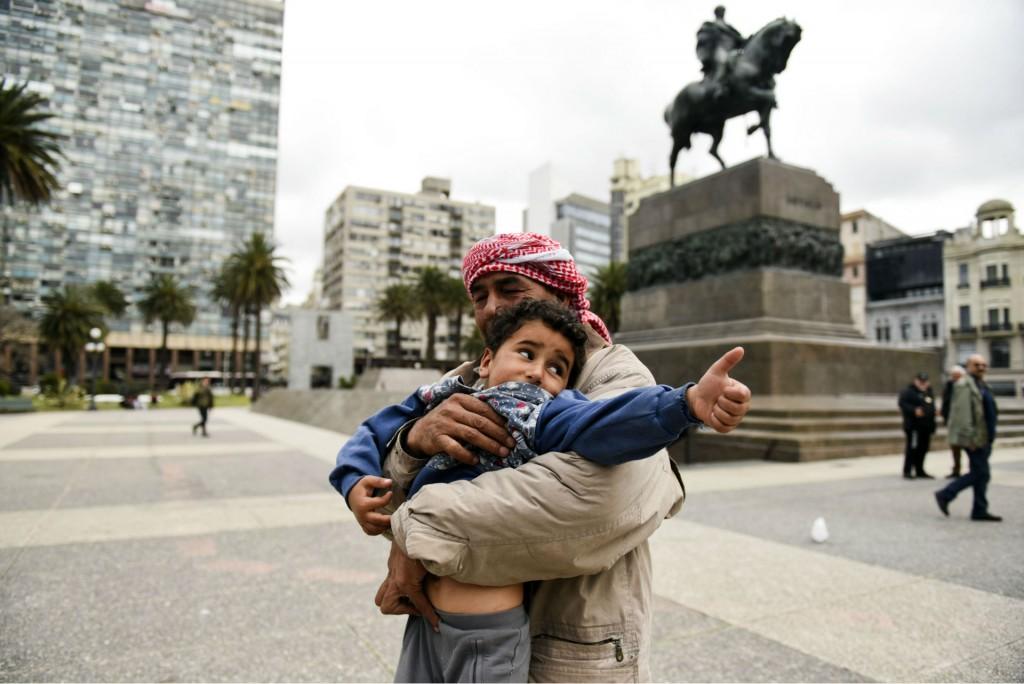 Un refugiado sostiene a su hijo en la Plaza Independencia, en Montevideo (AP)