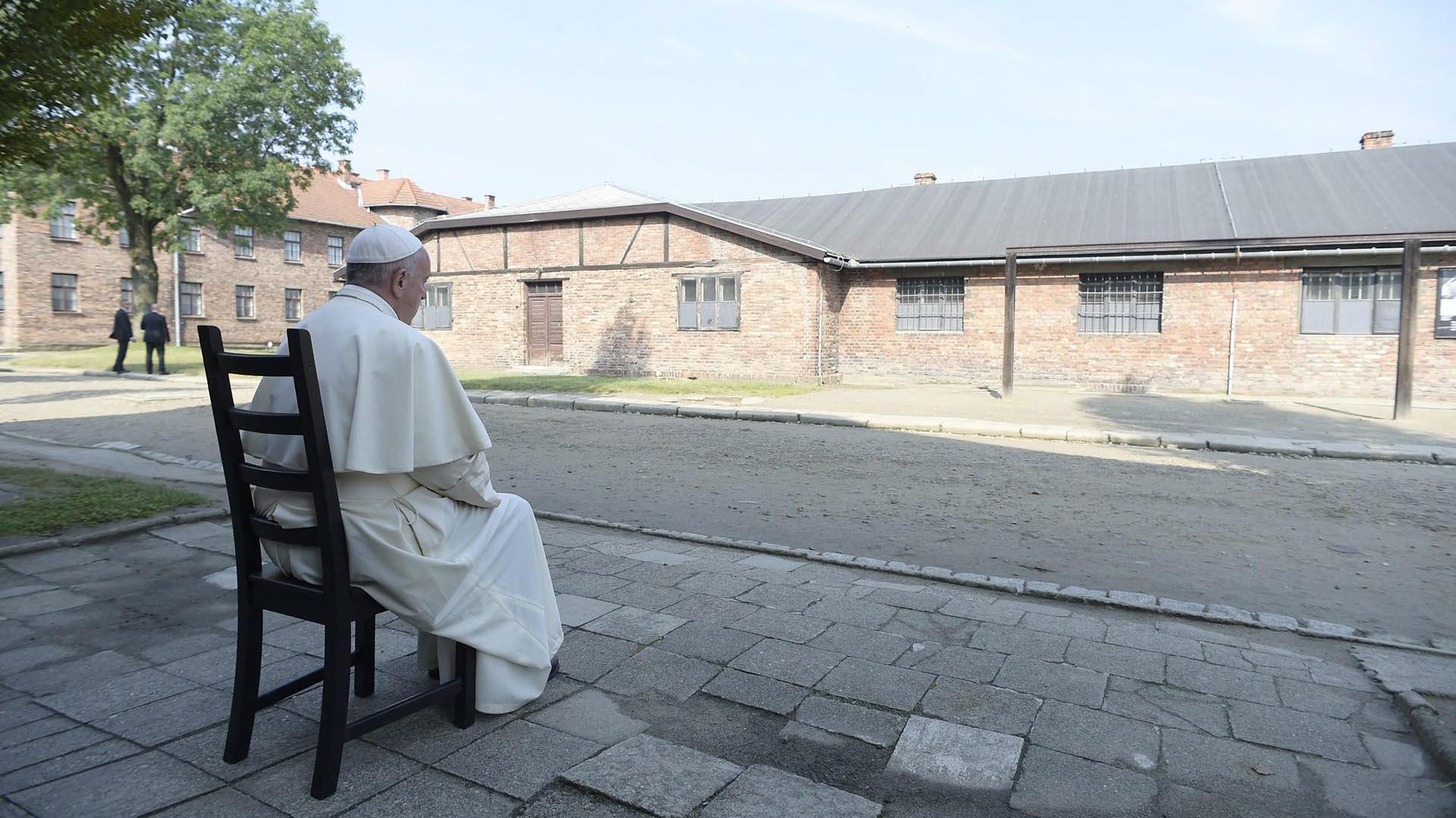 Francisco sentado frente a un barracón durante su visita al campo de concentración nazi de Auschwitz (EFE)