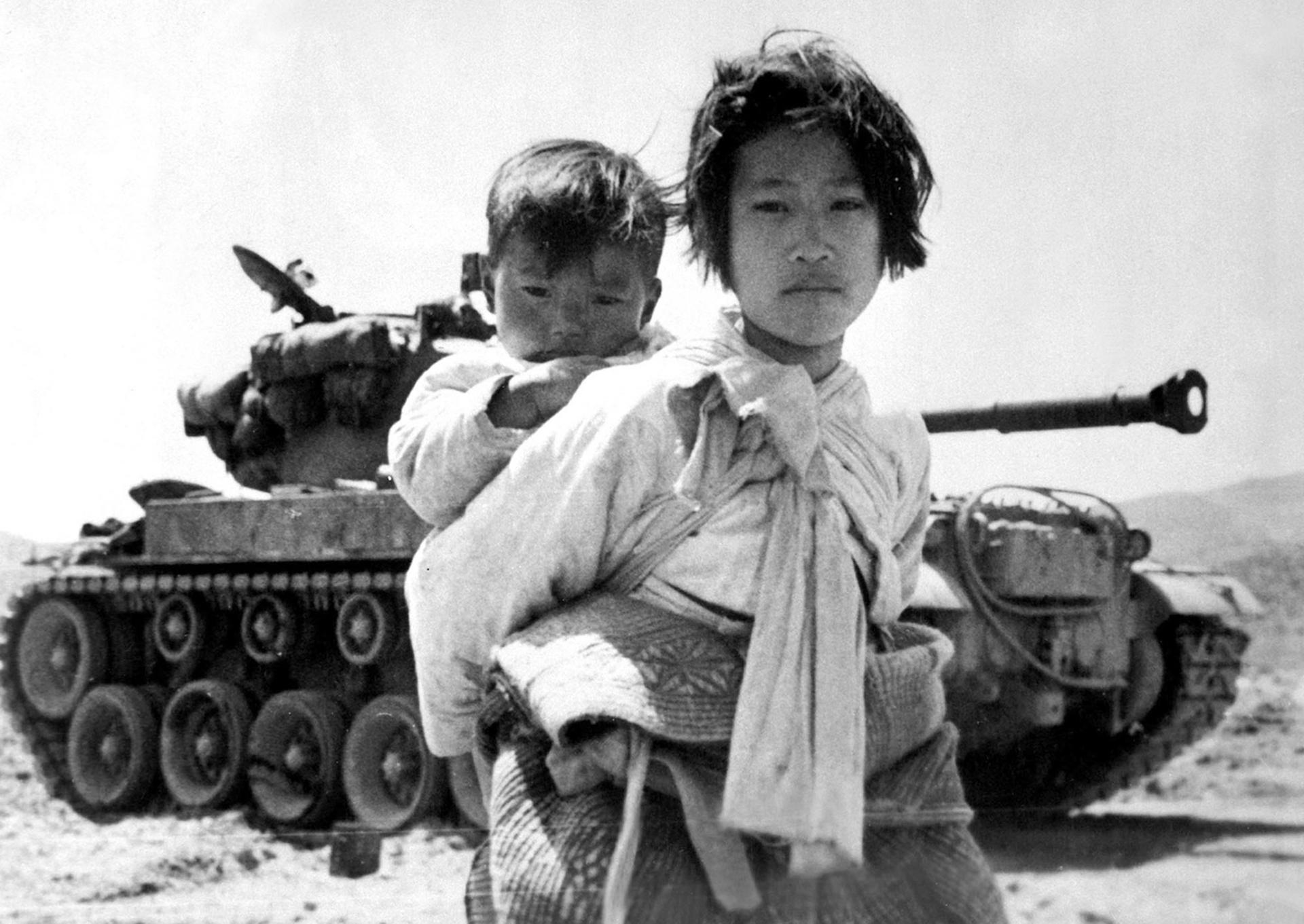 Con su hermano en la espalda, una cansada niña de la guerra coreana, en Haengju, Corea. El 9 de junio de 1951 (US Navy)