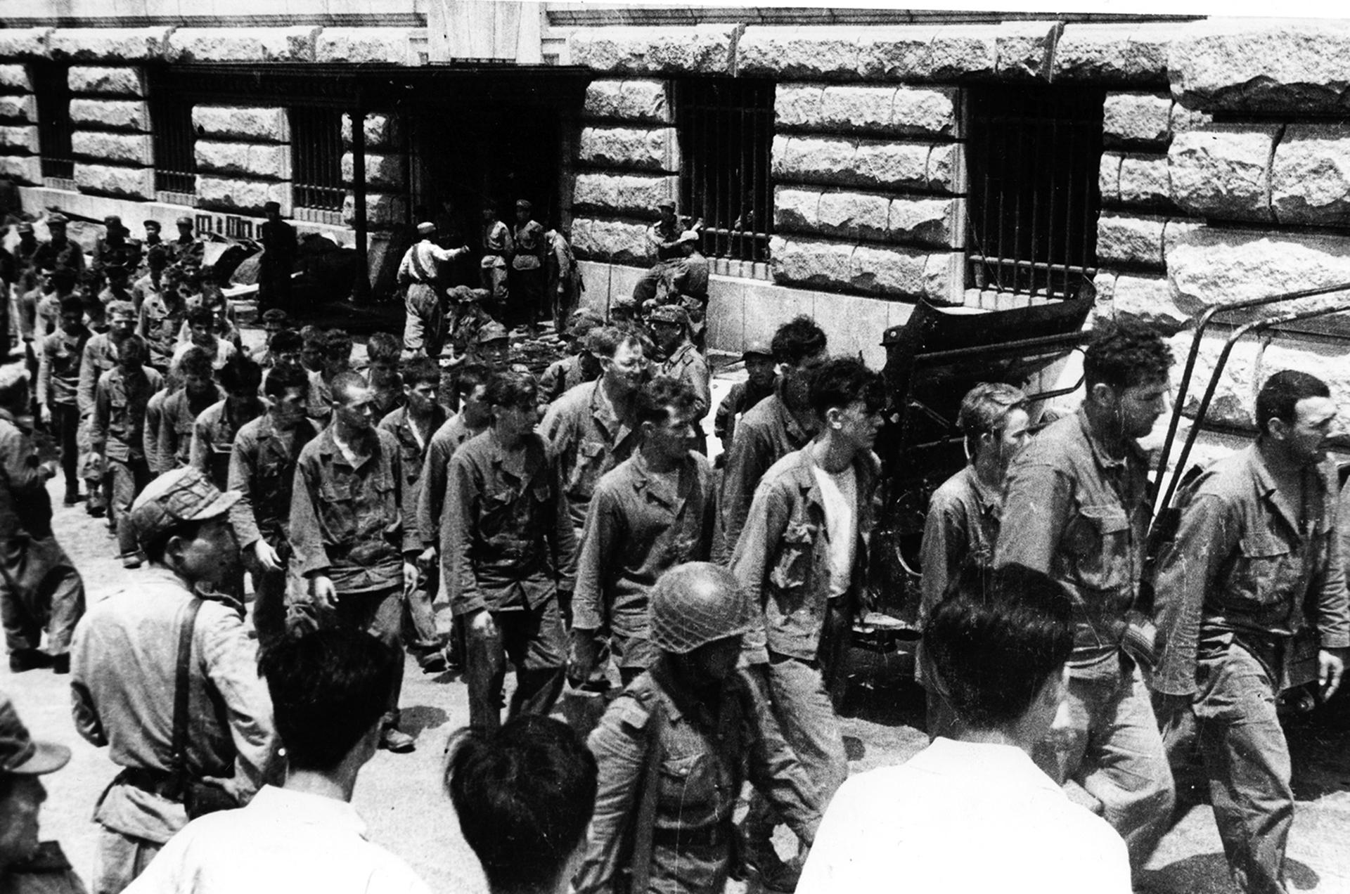Combatientes estadounidenses capturados durante la guerra de Corea marchan por una calle (AP)
