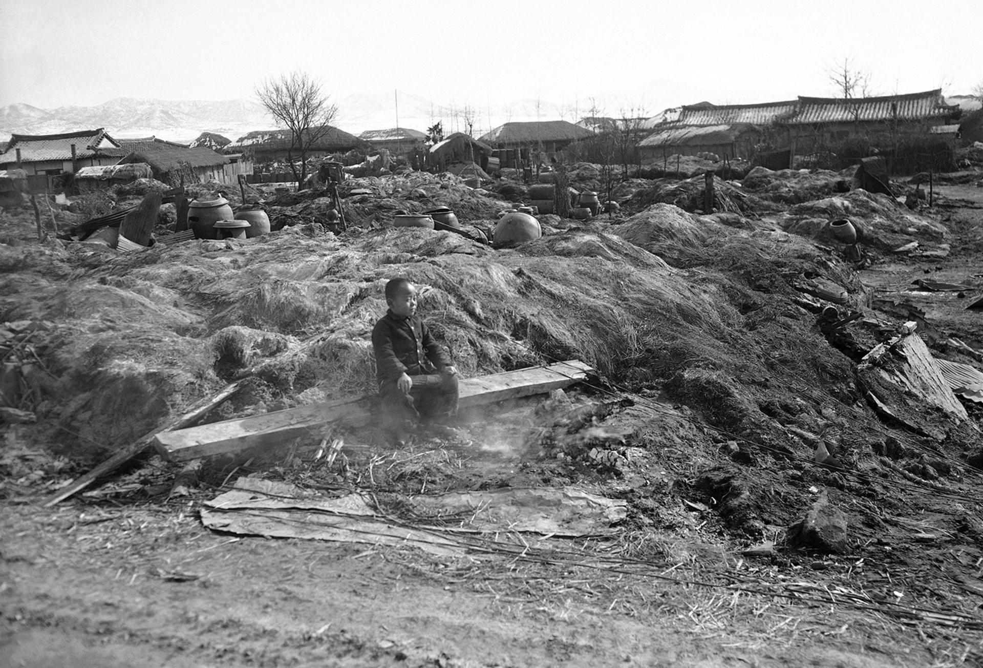 Un niño sentado en las humeantes ruinas de su casa destruida por el fuego en la zona de Suwon el 3 de febrero de 1951, cuando las tropas aliadas quemaron viviendas que podrían proporcionar refugio a las tropas rojas (AP)